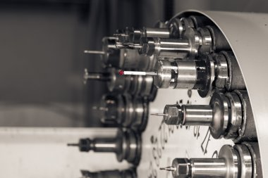 Rotating head with tools at CNC lathe in workshop