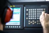 CNC operátor, mechanických technik pracovník v kovoobrábění frézovací centrum v nástrojárně vkládání dat s klávesnicí na sobě hluk cancelling sluchátka