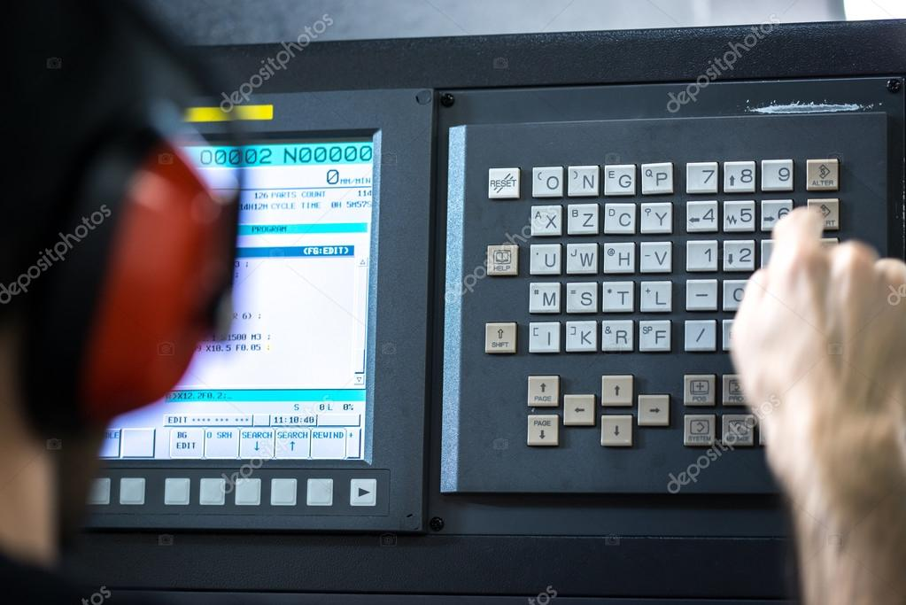 CNC operator, mechanical technician worker at metal machining milling center in tool workshop inserting data with keyboard wearing noise cancelling headset