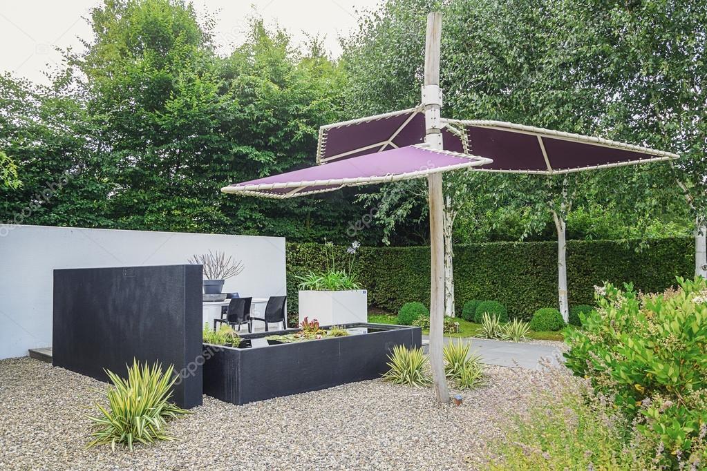 Garten mit trendigen Teich, moderne Gartenmöbel und Sonnenschirm ...