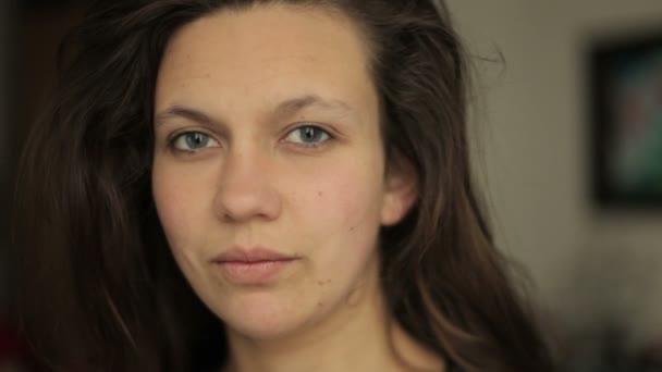 Mladá žena hledá zvědavě a svůdně do kamery