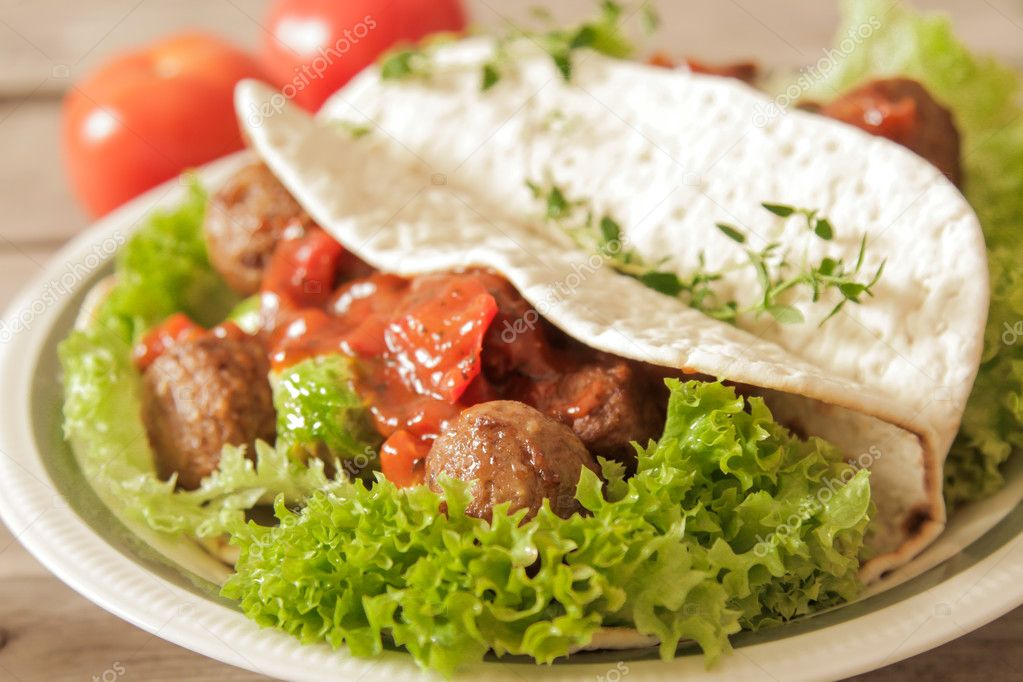 meatballs with cabbage on lettuce in pita bread