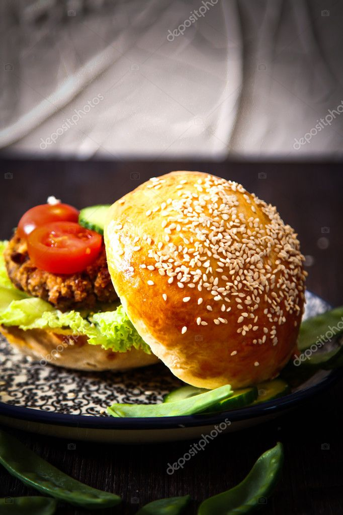 homemade veggie burger in a bun with sesame seeds of beer.