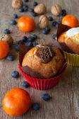 Fotografie Schokolade und Vanille-Zitronen-Muffins mit Mandarinen und Walnüssen