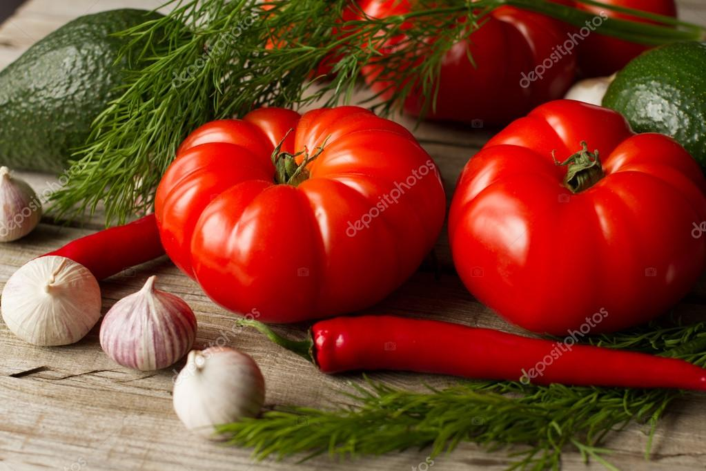 Tomato with avocado and garlic with dill. on wood background