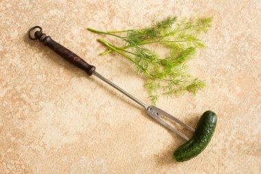 Old vintage fork for meat and green cucumber