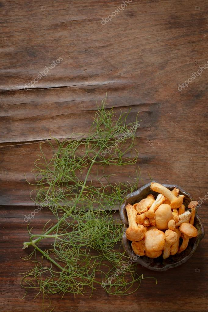 chanterelles with chili pepper and dill on a wooden table