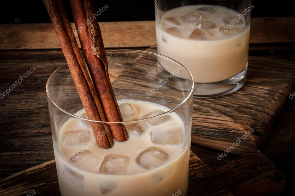 Irish cream liqueur in a glass with ice and cinnamon