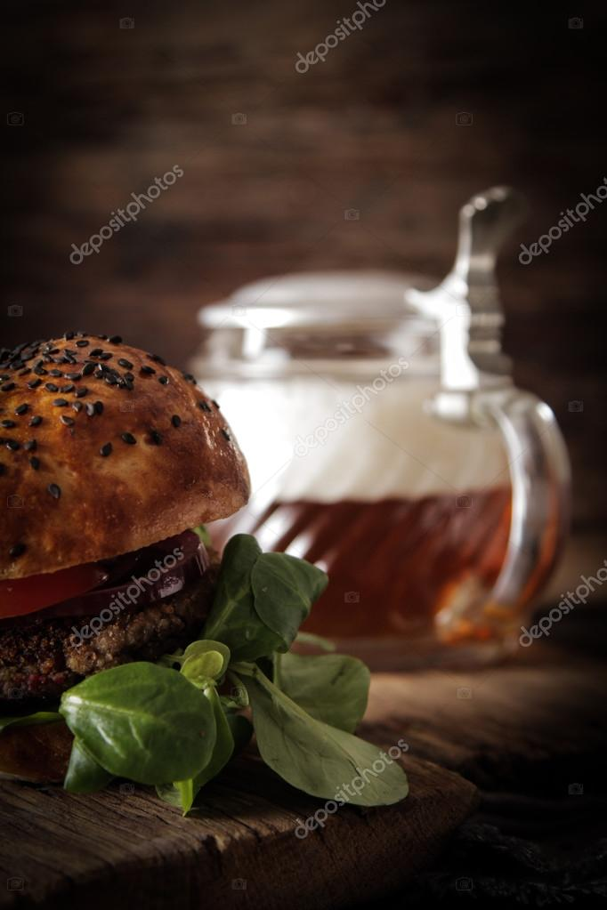 homemade veggie burger in a bun with sesame seeds of beer. delic