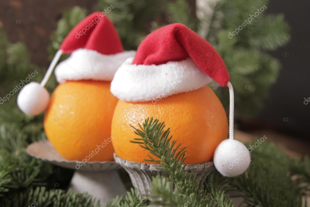 e08359caf0c25 Naranjas en gorros de Navidad rojos sobre un fondo de ramas verdes de  árboles de Navidad