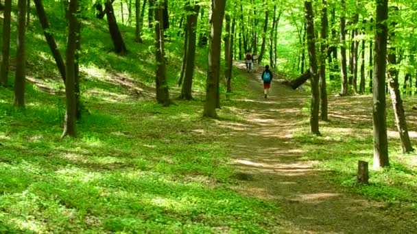 Young people walk in a lush green spring forest