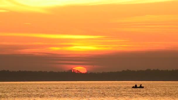 Motorový člun se pohybuje na vodě při východu slunce se slunce na obzoru