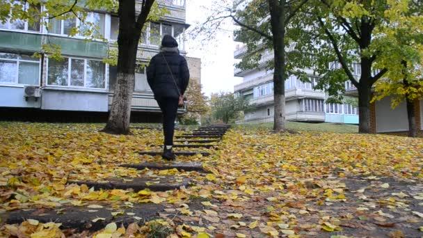 Dívka v černém oblečení a botách chodí na pěší na podzim