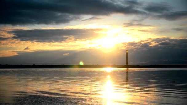 Efektní východ slunce nad vodou, s majákem