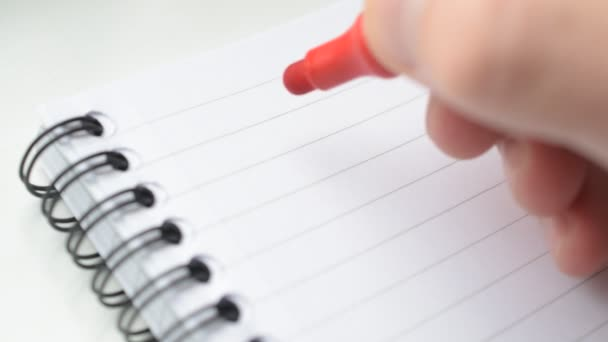Mano che scrive gli obiettivi con lindicatore rosso nel blocco note