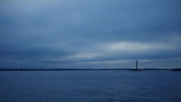 Dynamic clouds move fast over water and lighthouse