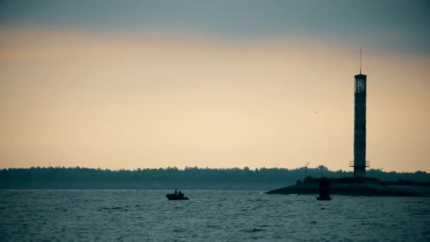 Siluety dvou mužů ve člunu poblíž Maják za soumraku