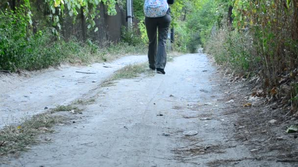 Woman in trousers with backpack walks away from camera
