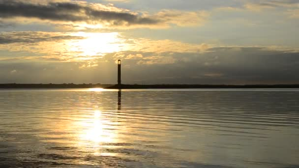 Water landscape with lighthouse and yellow clouds at dawn