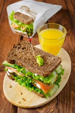 Club sandwich with salmon and cucumbers