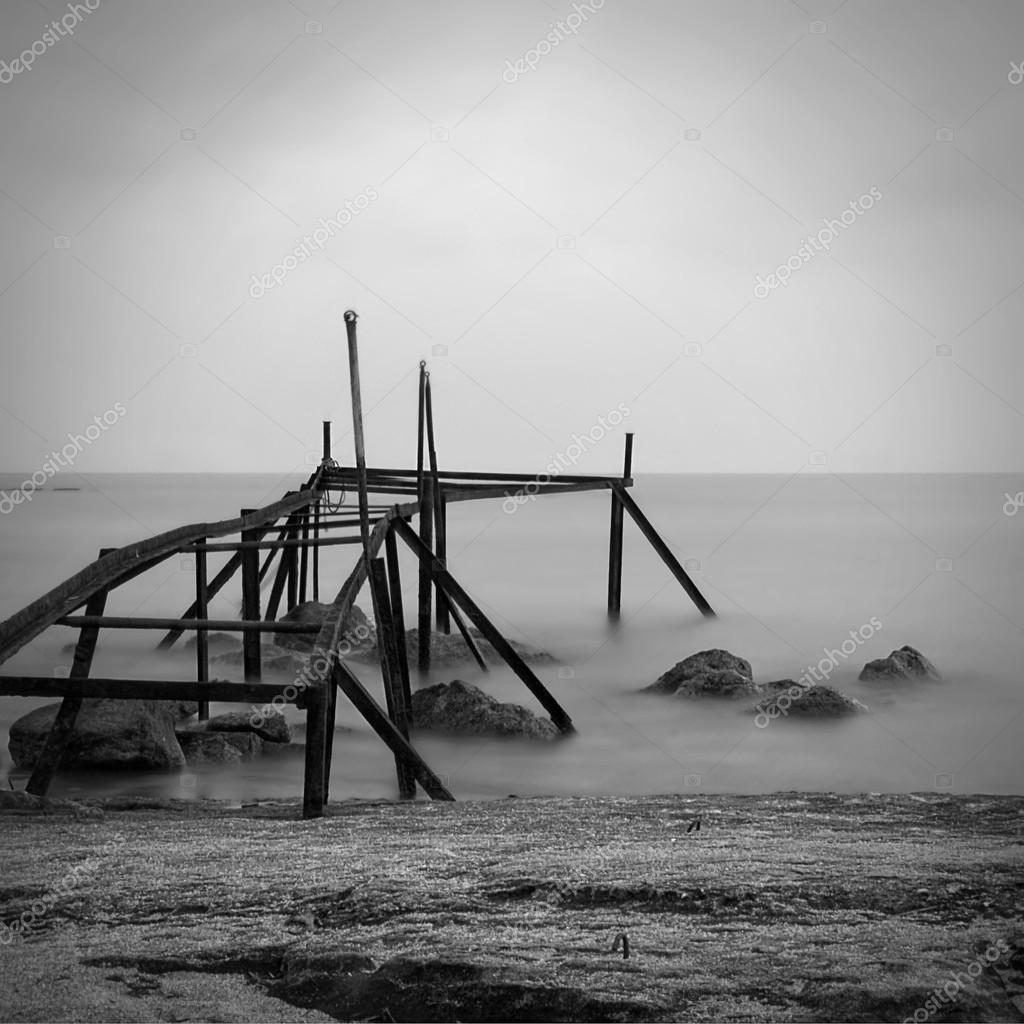 Black and white seascape with destroyed pier