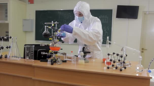 Chemical laboratory. A scientist wearing a respirator and a protective suit conducts chemical experiments. Chemical analysis of substances.