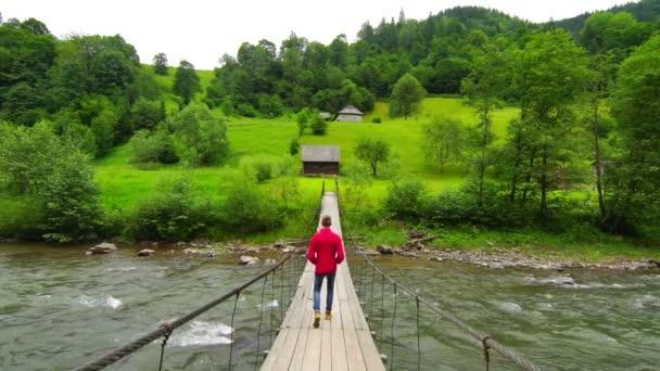 Muž pěšky přes visutý most.