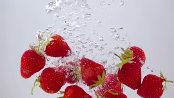 Zralé jahody padají do vody. Světelné pozadí. Pomalý pohyb.