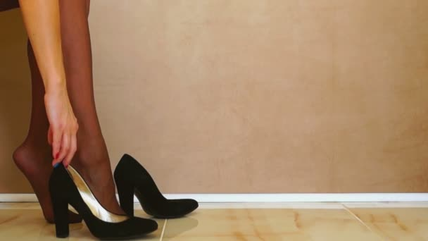 Frau zieht schwarze Schuhe an
