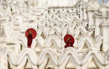 Burma,The Novice monk holding red umbrella on the pagoda