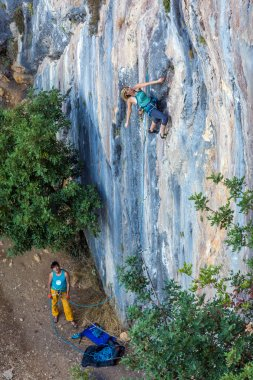 Two Climbers work in pair on vertical rocky Wall