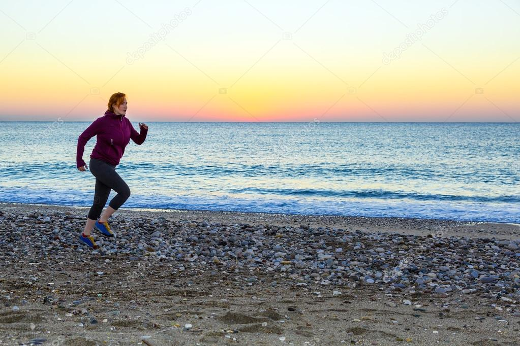 Young Woman jogging on Seafront making Morning Fitness