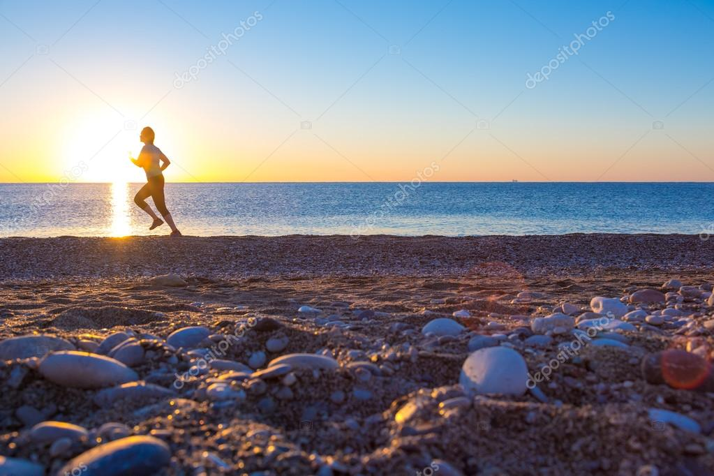 Silhouette of Sportswoman on Ocean Beach at Sunrise