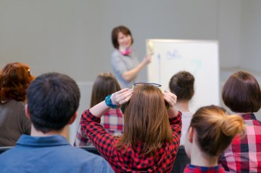 Group of Students Listening Lecturer staying at Flip Chart