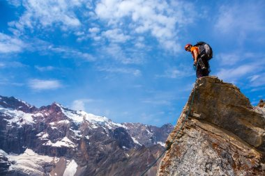 Alpine Climber staying on rocky Cliff