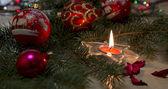Fényképek Szilveszter összetétele égő gyertyát, és a fa ág