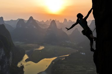 Elegant female extreme climber silhouette against the sunset over the river