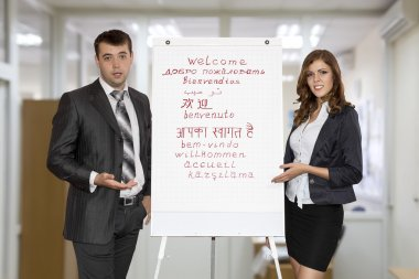 Male and female instructors welcomes attendants pointing on the flip chart
