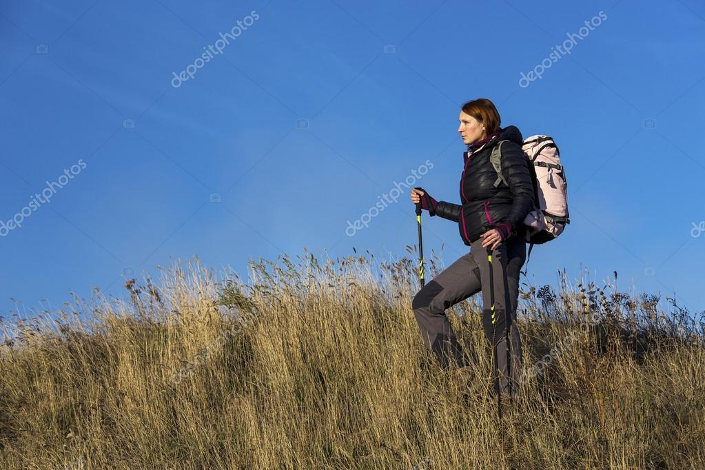 Female backpacker ascends steep hill