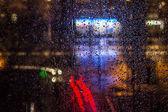 Esőcseppek az ablakon, a városi éjszakai fények