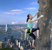 Weiblichen Kletterer über die Skyline der Stadt
