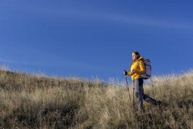 Female hiker walks grassy hill