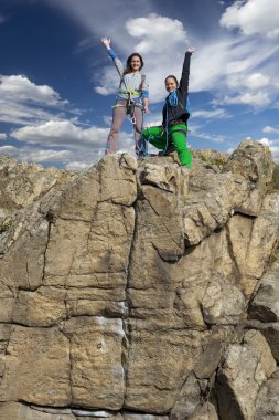Group of two happy female climbers  celebrates the victory
