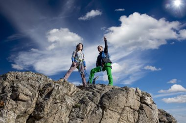 Two female climbers observing the landscape from summit