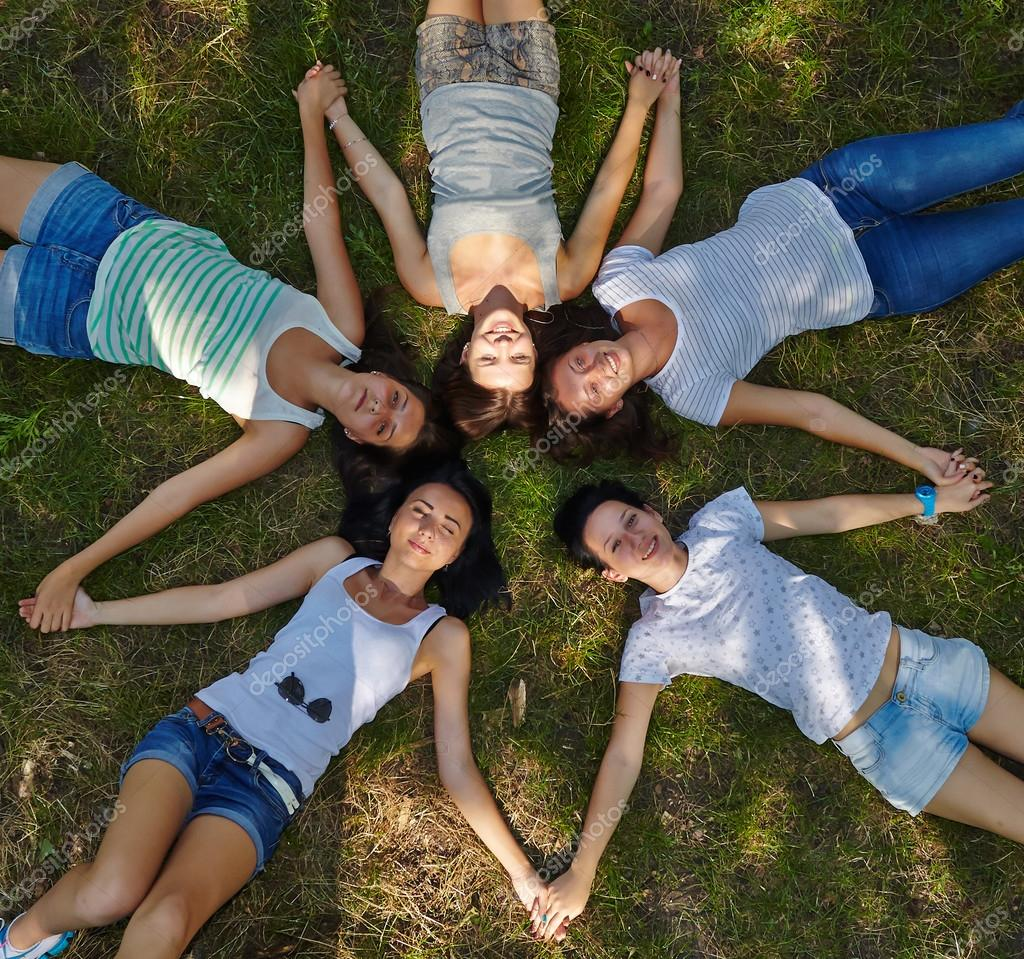 Five young ladies lounging on grassy lawn
