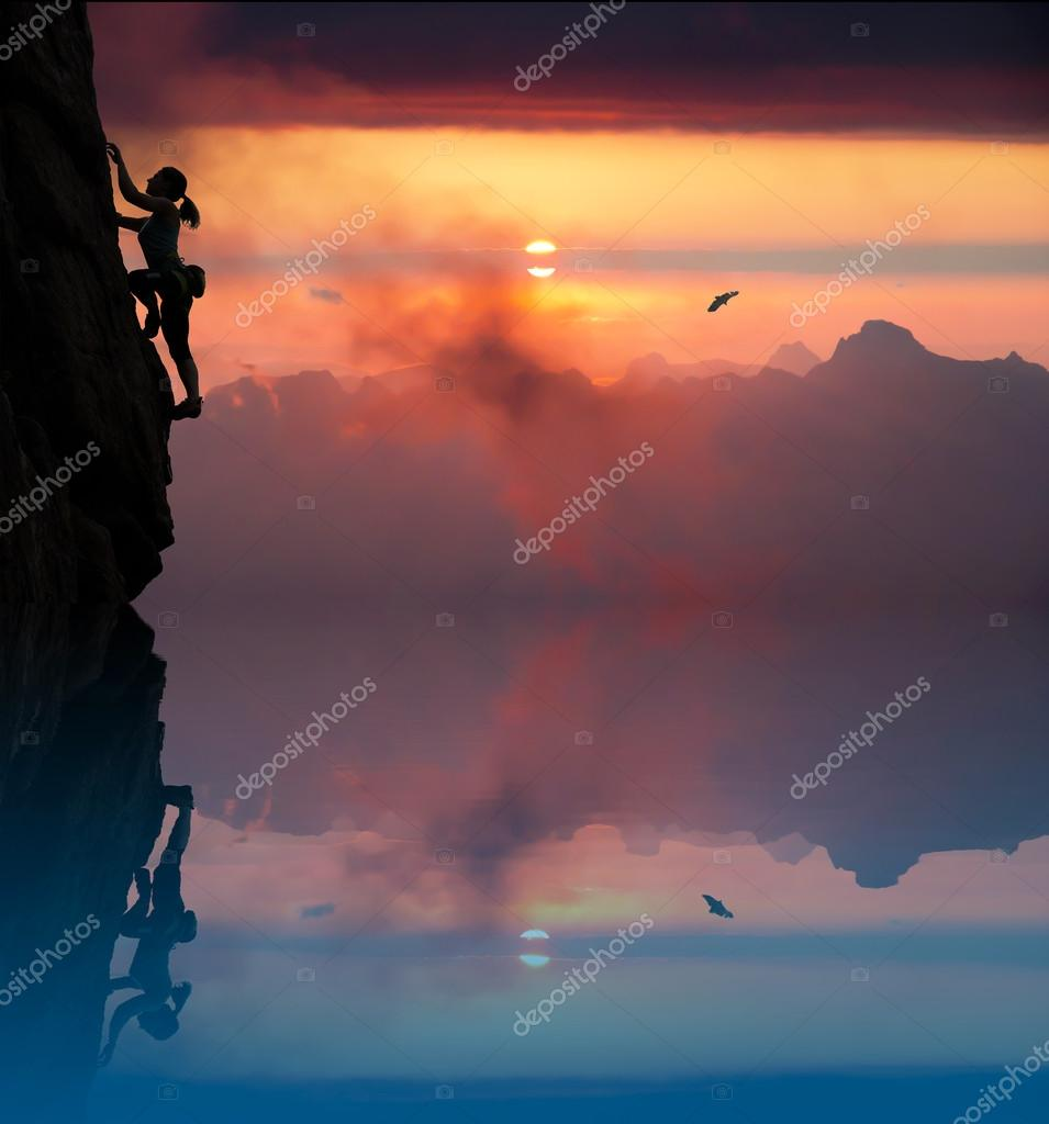 Silhouette of elegant female climber with lake and dusk
