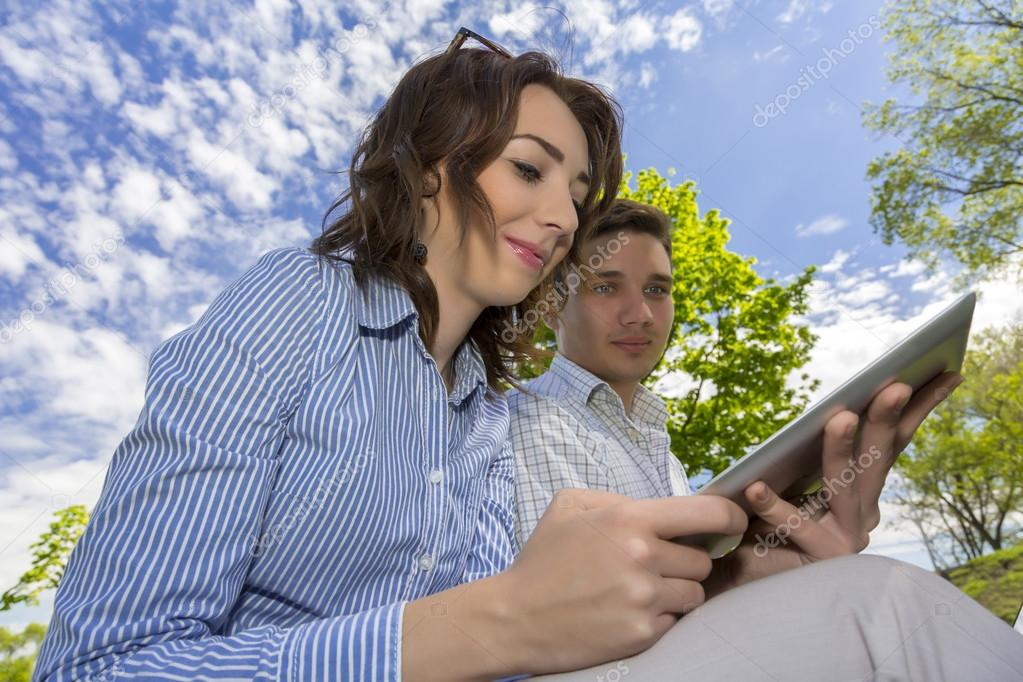 Man and woman with tablet PC on blue sky background