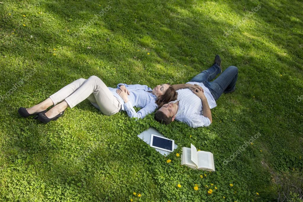 Two people napping on grassy lawn