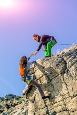 Female climbers helping each other on rock wall