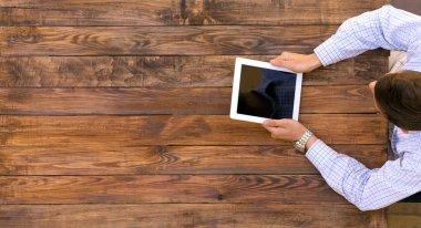 Man holding tablet PC sitting at vintage handcrafted wooden desk